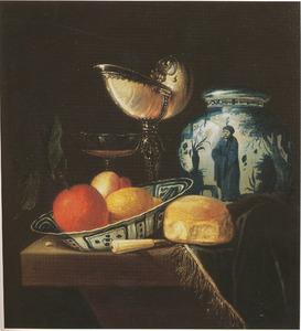 Stilleven met een nautilusbeker, porseleinen dekselpot en schotel met vruchten