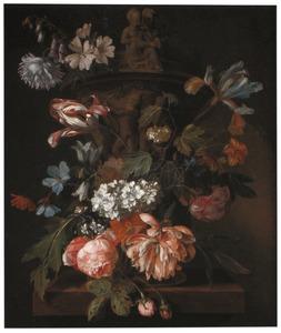 Schikking van bloemen rond een geornamenteerde tuinvaas op een stenen plint