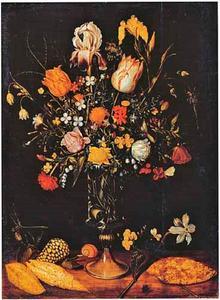 Bloemen in en rond een hoge glazen vaas, met schelpen, op een stenen plint