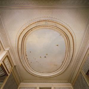 Stucplafond voorzien van een ovaal middenveld met wolkenlucht en vogels