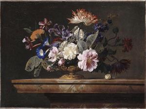 Bloemen in een glazen vaas met metalen voet op een marmeren blad