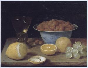 Stilleven met een roemer, vruchten en noten op een tafel