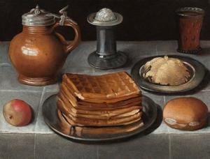 Wafels en boter op tinnen borden met een appel, een broodje, een kruik, zout en een gegraveerd bierglas op een gedekte tafel