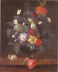 Bloemen in een glazen vaas en een vogelnestje op een marmeren blad