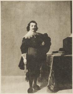 Portret van een man, staande ten voeten uit bij een tafel in een interieur