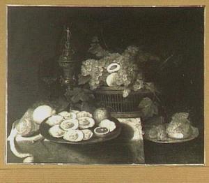 Stilleven van een mand met vruchten, schaal met oesters en een pronkbeker