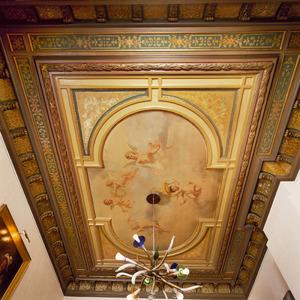 Zwevende putti omgeven door gestucte en geschilderde decoraties