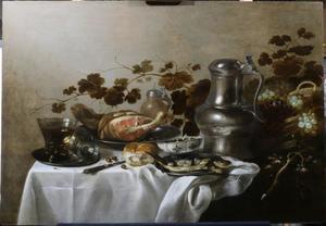 Stilleven met drinkegerei, een ham, een haring en druiven op een gedekte tafel