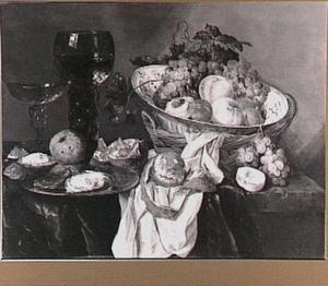 Stilleven met een porseleinen schaal in een mand, roemer, wijnglas, vruchten en oesters op een donker tafelkleed met wit servet