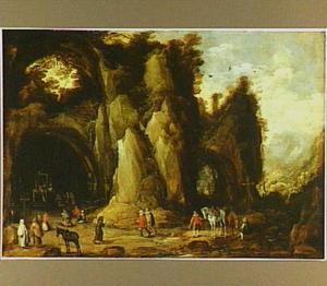 Pelgrims tijdens een religieuze plechtigheid in de grot van een heremiet; op achtergrond een rotsachtig landschap