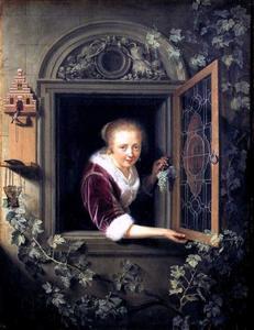 Jonge vrouw met een tros druiven in een venster