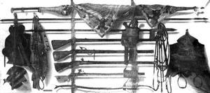 Trompe l'oeil met aan de wand hangende schietwapens, een vaandel, een zadel, een hoofdstel, stijgbeugels en andere krijgsparafernalia