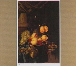 Een schotel met vruchten en een roemer met wijn op een met een groen kleed bedekte tafel