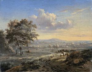 Heuvelachtig landschap met een ruiter op een landweg