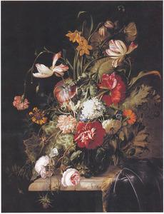 Bloemen in een glazen vaas op een deels met een tafelkleed bedekte marmeren plint