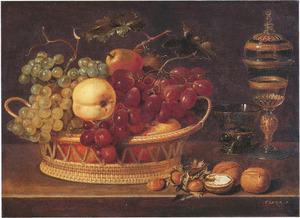 Stilleven van vruchten in een mand, met noten en een glazen bokaal, op een stenen plint