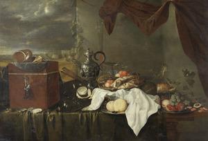 Stilleven met metalen schenkkan, vruchten en een gebraden kalkoen, met doorkijk naar een landschap