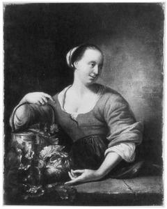 Een vrouw met een emmer groente achter een toonbank