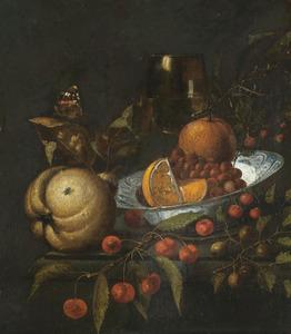 Een roemer en vruchten in en rondom een porseleinen kom op een stenen plint
