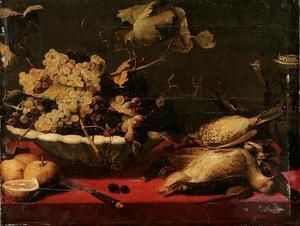 Stilleven met een plooischotel met druiven, citrusvruchten, gevogelte en een tuitkan op een met een rood kleed bedekte tafel