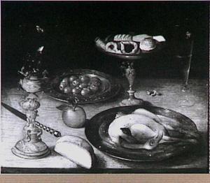 Stilleven met gebraden kip, tazza met zoetigheden, een bordje olijven, een bekerschroef eneen sinaasappel