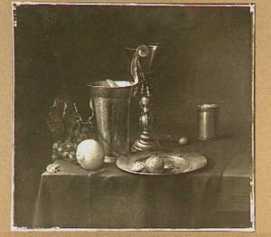 Stilleven van roemer in bekerschroef, siervaatwerk en vruchten op een tafel