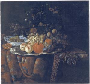 Vruchtenstilleven op en marmeren tafel met een oosters kleed