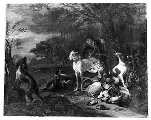 Honden en jager bij jachtbuit in een landschap, met jagende mannen op de achtergrond