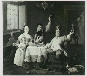 Familie, etend en drinkend in een interieur