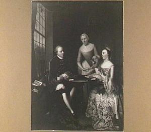 Man en vrouw spelen kaart aan een kleine tafel voor een venster, achter hen schenkt een dienstmeid koffie