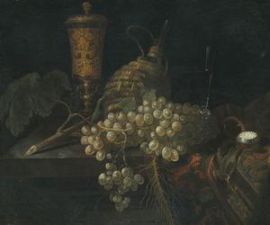 Stilleven met onder meer een tros druiven, een mandfles, een bokaal en een horloge gerangschikt op een deels met een oosters kleed bedekte plint