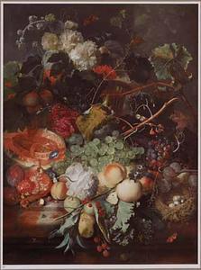 Vruchtenstilleven op een marmeren blad, met rechts een vogelnest en bovenin een mand met bloemen