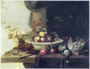 Stilleven met een roemer, vruchten en dood gevogelte, met doorzicht op een