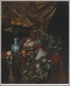Rijk stilleven van vruchten, een akeleibeker, een roemer en een porseleinen kan op een gedekte tafel