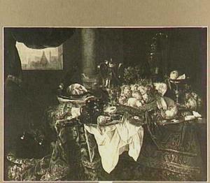 Pronkstilleven met fruit, etenswaren, zilver-en glaswerk, nautilusbeker en porselein op een Oosters kleed met wit servet; op de achtergrond een doorkijkje over een stad