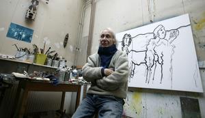 Jan Sierhuis met een van zijn schilderijen in zijn atelier