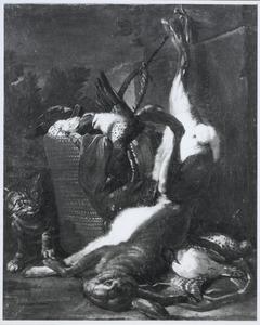 Kat bij jachtbuit van een opgehangen haas en gevogelte in en bij een mand
