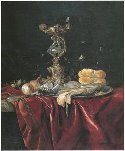 Pronkstilleven met een Orpheus zoutvat, glaswerk, brood, vis, uien en een hazelnoot op een donker kleed