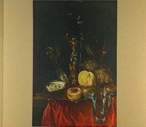 Stilleven met bekerschroef, roemer, glas- en siervaatwerk, horloge en vruchten op een rood kleed