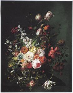 Bloemstuk van velerlei bloemen op een stenen tafel