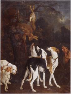 Meute jachthonden onder een boom waarin de opgehangen jachtbuit