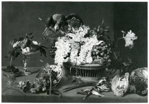 Een stillleven met dode vogels, een papegaai, een rieten mand en een tazza met fruit op een tafel