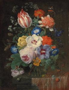 Bloemen in een glazen vaas op een deels met een tafellaken bedekt stenen plint