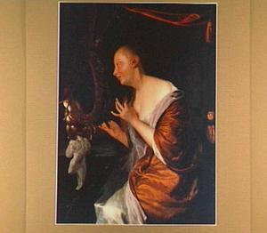 Een jonge vrouw haar haar kammend voor een spiegel