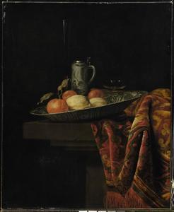 Stilleven van fruit in een porceleinen schaal, een Delfts-blauwe pul, wijnglazen en een  tafelkleed