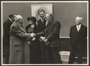 Adriaan van Zeegen (midden, met baard) en Jan Sluijters (links, met baard) schudden elkaar de hand op overzichtstentoonstelling Sluijters, Den Haag 1941