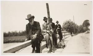 De Scheveningse antiquair Jurriaan Bruyne (met grijze baard en hoed) en drie mannen op een brugleuning