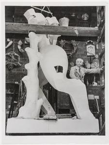 Ossip Zadkine staand bij het gipsmodel van zijn beeld De verwoeste stad in de gieterij Rudier te Parijs
