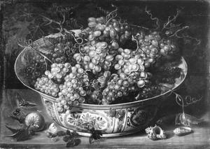 Chinese schaal met druiven op de voorgrond schelpen en vlinders