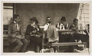De Scheveningse antiquair Jurriaan Bruyne (met grijze baard en hoed) en vier mannen op een terras